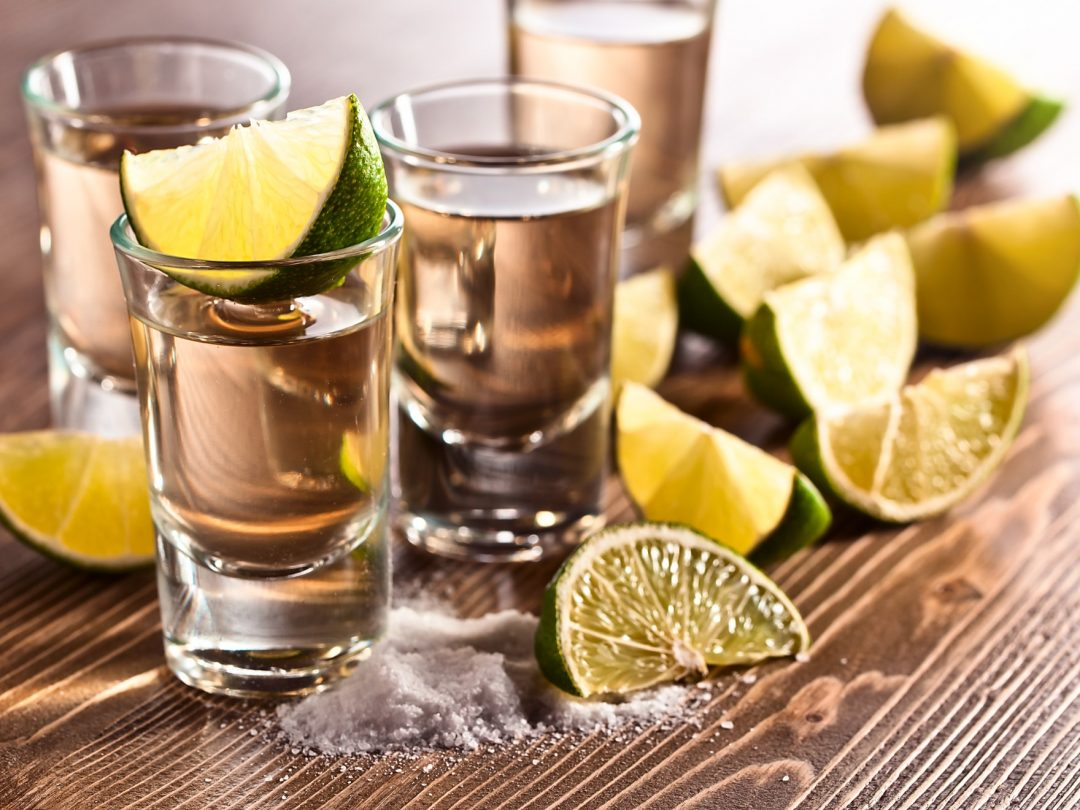 4 glasses of tequila with slices of lime and a small pile of salt - El Rincon Texas