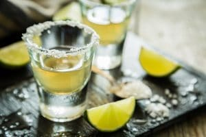 Gold tequila shots on rustic wood background - El Rincon